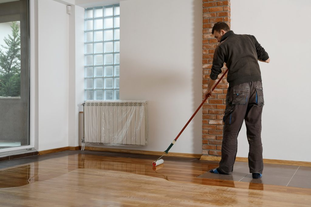 Worker uses a roller to coating timber floors.